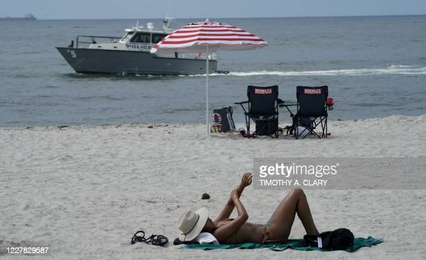 People relax on the beach next to the ocean as a Nassau County Police Marine Unit boat patrols the waters at Nickerson Beach Park in Lido Beach New...