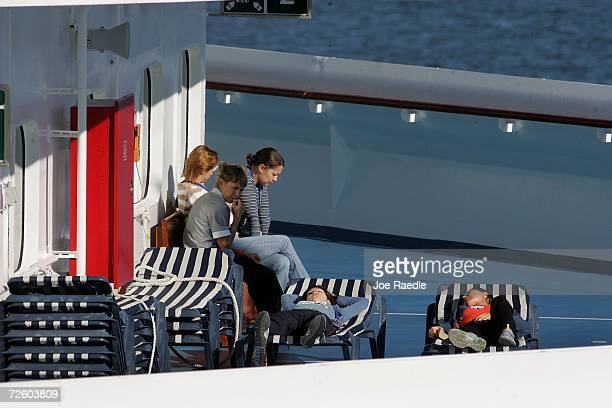 People relax on the deck of the Carnival Liberty Cruise ship as they wait to disembark from the ship at Port Everglades on November 19 2006 in Fort...