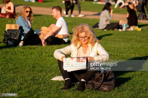 People relax on the grass as the sun shines in Green Park in central London on February 26 as Britain experienced record temperatures for a winter...