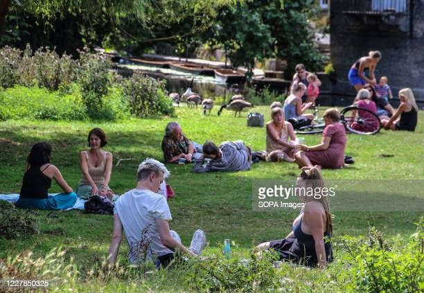 People relax on the grass on a warm summer day. People relax during the warm summer weather as the temperature in England is expected to reach 30...
