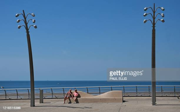 TOPSHOT People relax on the promenade beside the beach in Blackpool on the northwest coast of England on May 31 2020 on the eve of a further...