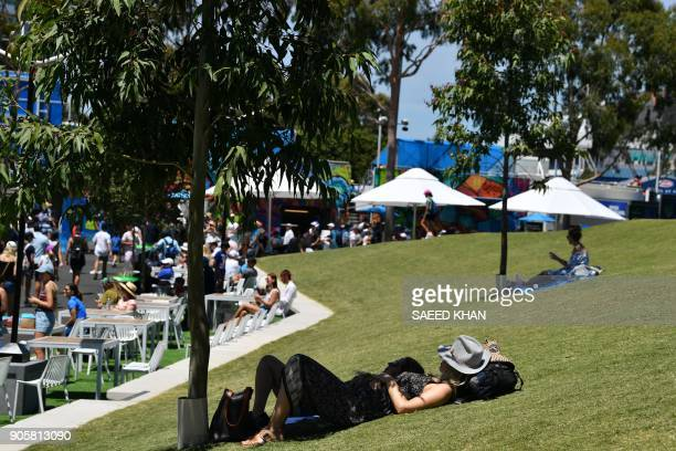 People relax under a tree on day three of the Australian Open tennis tournament in Melbourne on January 17 2018 / AFP PHOTO / SAEED KHAN / IMAGE...