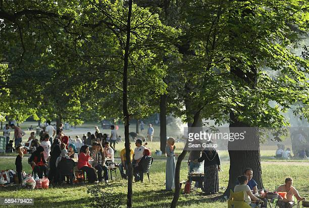 People relax while picnicking and grilling meat in Schlesischer Busch park on a warm summer evening on July 10 2016 in Berlin Germany While fall and...