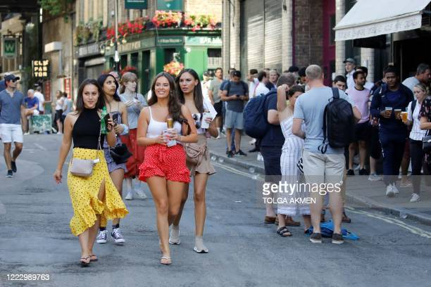 People relax with takeaway draught beer in plastic cups at the end of the day ,at the Borouhg Market in London on June 26 as temperatures reached 31...