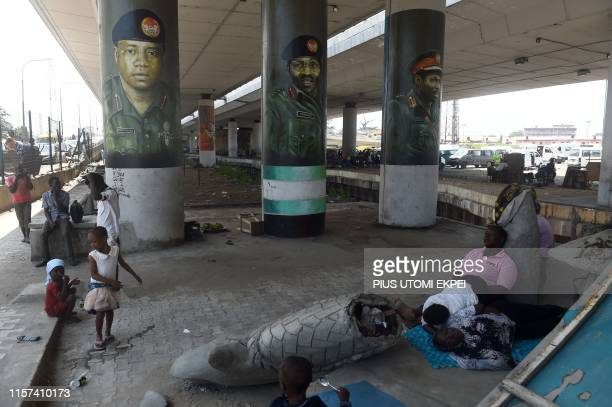 People relaxes beside portraits of President Mohammadu Buhari former Presidents Ibrahim Babangida and Olusegun Obasanjo painted in army uniforms...