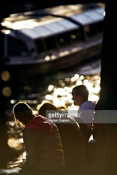 people relaxing along canal. - merten snijders stockfoto's en -beelden