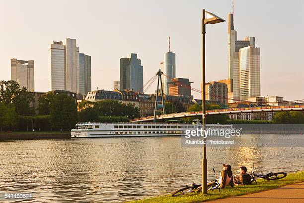 People relaxing along river Main, with the Holbeinsteg footbridge and the city in the background, Frankfurt, Germany
