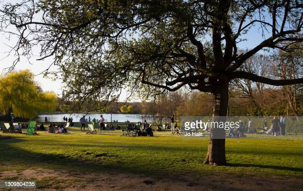People relaxing and socialising in Regents Park on a warm Spring Day on March 29, 2021 in London, England. Today the government eased its rules...