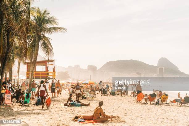 people relaxing and sunbathing at famous copacabana beach, rio de janeiro, brazil - copacabana beach stock pictures, royalty-free photos & images