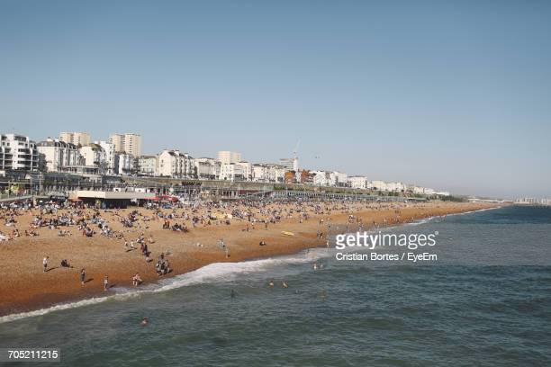 people relaxing at beach against clear sky on sunny day - bortes photos et images de collection