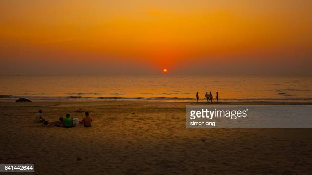 People relaxing at beach during sunset