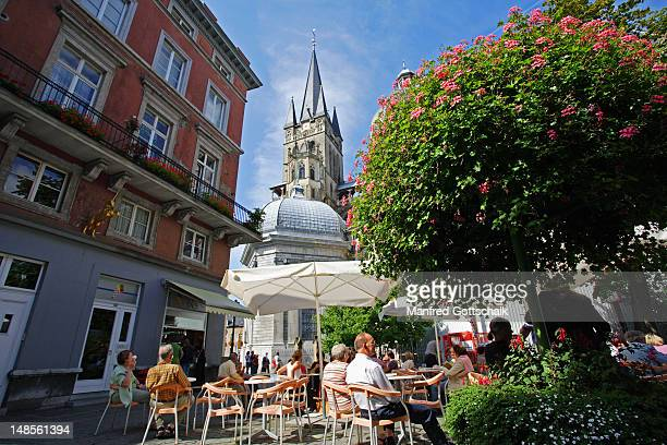 People relaxing at outdoor cafe in Munsterplatz, near Aachen Dom (Cathedral).