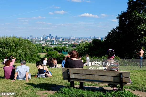 People relaxing at parliament hill in Hampstead Heath Park against London's skyline