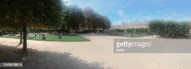 People relaxing at the Place des Vosges square on a sunny summer day, Paris