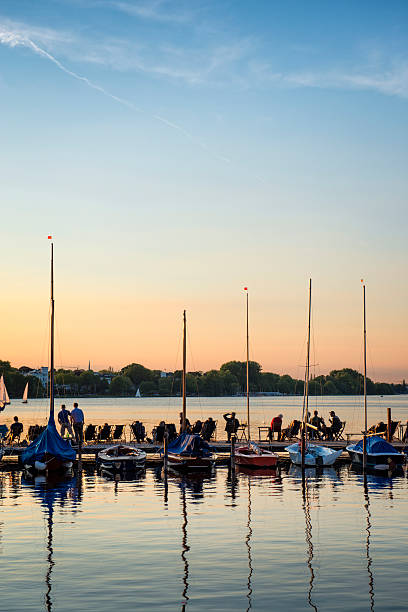 People relaxing at yacht harbor at sunset
