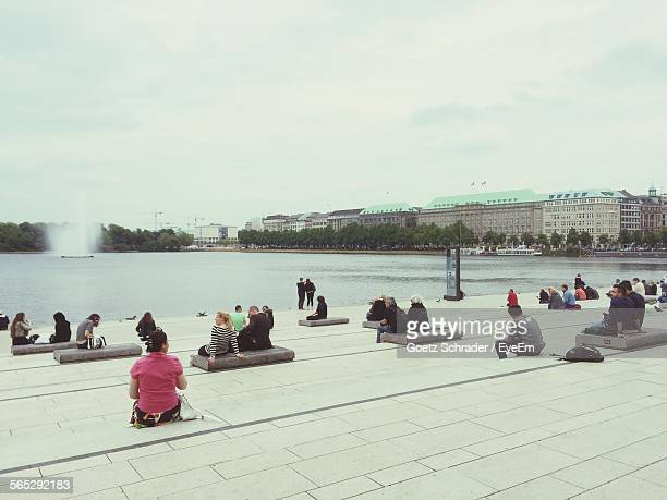 People Relaxing By Alster River Against Sky
