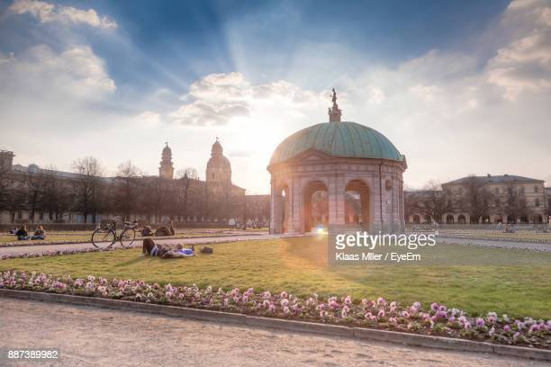people relaxing by pavilion in park against cloudy sky on sunny day - upper bavaria stock photos and pictures