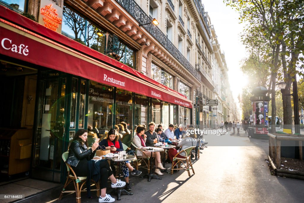 People relaxing, eating and drinking in restaurant in Paris, France : Stock Photo