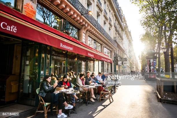 people relaxing, eating and drinking in restaurant in paris, france - pavement cafe stock pictures, royalty-free photos & images