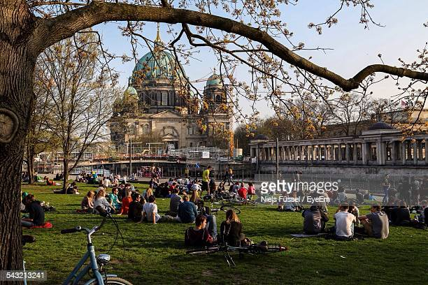 People Relaxing In Park With Berlin Cathedral On Background
