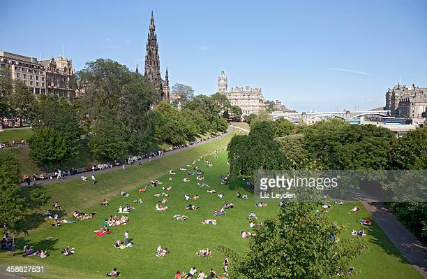 people relaxing in princes street gardens, central edinburgh. - balmoral hotel stock photos and pictures