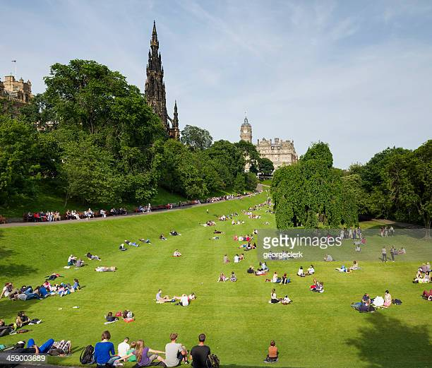 people relaxing in princes street gardens - new town edinburgh stock photos and pictures