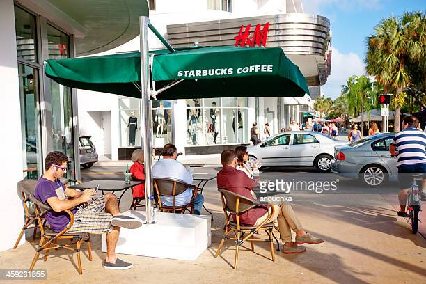 people relaxing in starbucks coffee, miami beach - lincoln road stock pictures, royalty-free photos & images