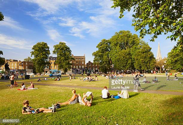 people relaxing in the sun, clapham common - park stock-fotos und bilder