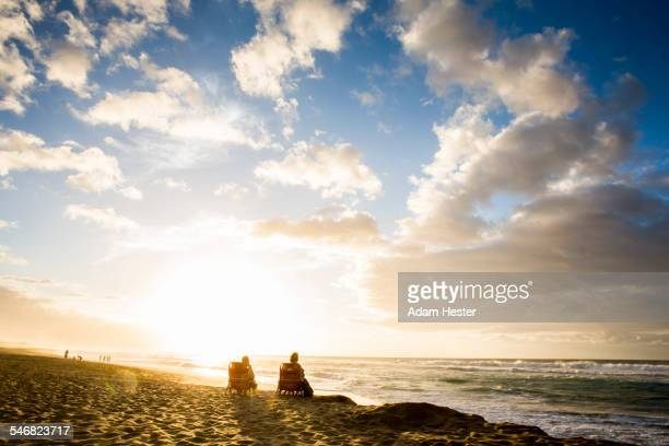 People relaxing on beach at sunrise