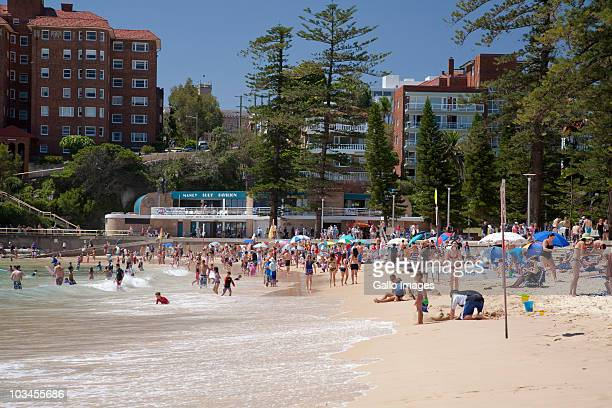 People relaxing on beach with Manly Surf Pavilion in background, Manly, Sydney, New South Wales, Australia