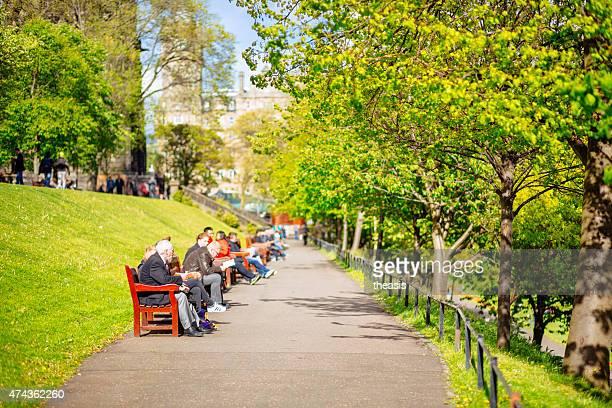 gäste entspannen auf bänken in der princes street gardens edinburgh - theasis stock-fotos und bilder