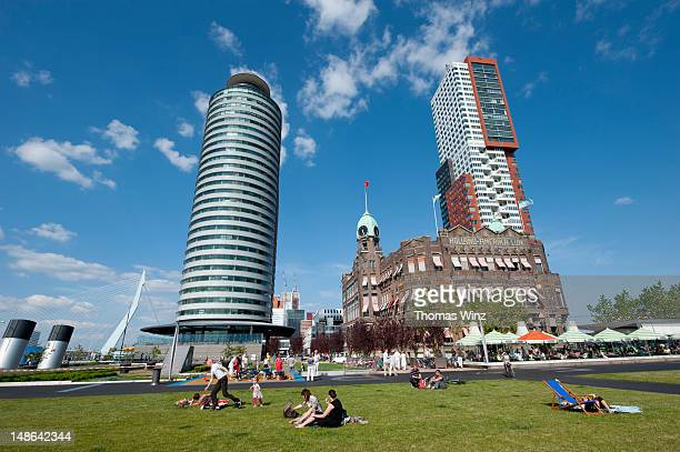 People relaxing on grass in front of Hotel New York World Port Centre and Montevideo building.