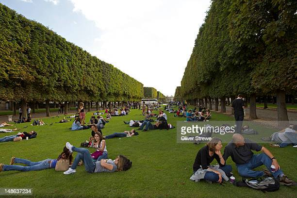 People relaxing on grass in Luxembourg Gardens.