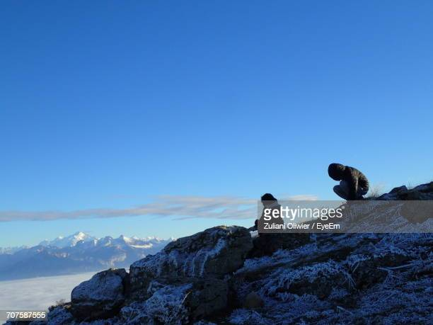 People Relaxing On Mountain Against Blue Sky