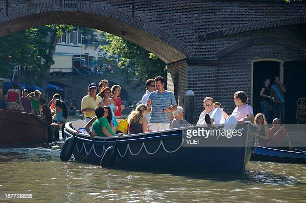 People relaxing on recreational boats in the canal Oudegracht