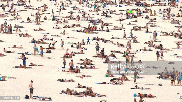people relaxing on sand at beach - crowded beach stock pictures, royalty-free photos & images
