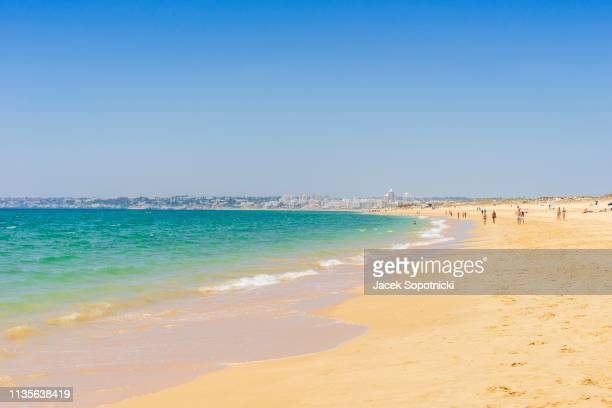 People relaxing on the beach next to Armacao de Pera, Algarve, Portugal