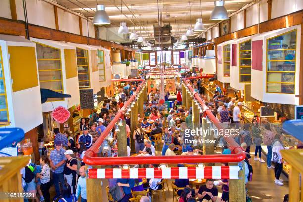 People relaxing, ordering food and eating at Public Market on Granville Island, Vancouver, British Columbia