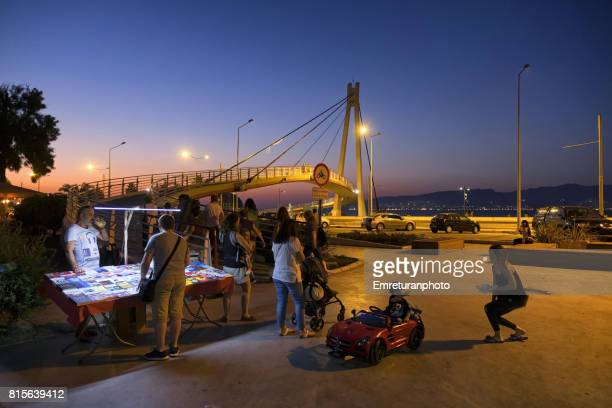 People relaxing outdoors at Goztepe district of Izmir near pedestrian bridge at sunset..