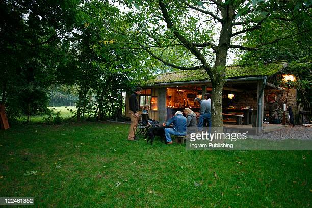 People relaxing outside a converted barn
