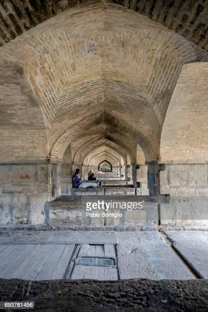 people relaxing under khaju bridge, isfahan, iran - ハージュ橋 ストックフォトと画像
