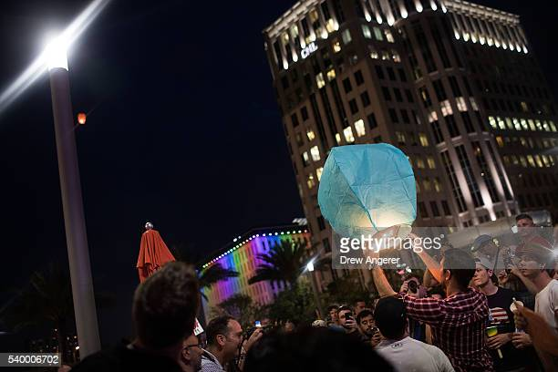 People release a lantern into the night during an evening memorial service for the victims of the Pulse Nightclub shootings at the Dr Phillips Center...