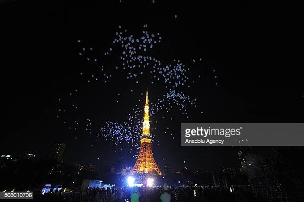 People release balloons carrying their personal wishes during an annual countdown event at the Prince Park Tower in front of Tokyo Tower illuminated...