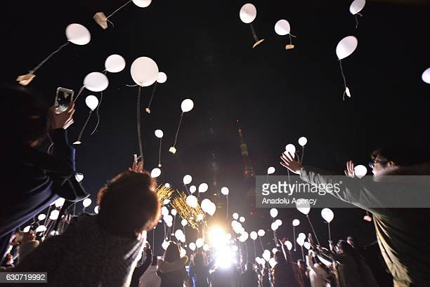 People release balloons carrying their personal wishes during an annual countdown event at the Prince Park Tower in front of Tokyo Tower to celebrate...