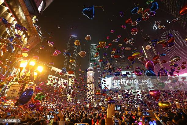 People release balloons during the New Year's Eve countdown event at Jiefangbei Pedestrian Street on January 1 2015 in Chongqing China