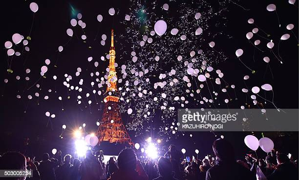 People release balloons to celebrate the New Year at the Prince Park Tower in Tokyo on January 1 2016 More than 1000 balloons were released carrying...