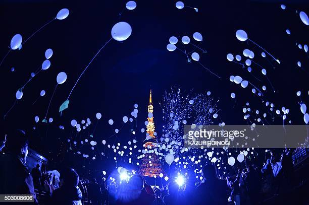 TOPSHOT People release balloons to celebrate the New Year at the Prince Park Tower in Tokyo on January 1 2016 More than 1000 balloons were released...
