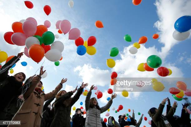 People release balloons to commemorate the third anniversary of the Great East Japan Earthquake and Tsunami near a coast damaged by the disaster in...