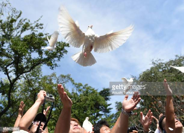 People release doves as they pay their respects to the war dead during a ceremony at the Yasukuni Shrine on August 15 2014 in Tokyo Japan Japan marks...