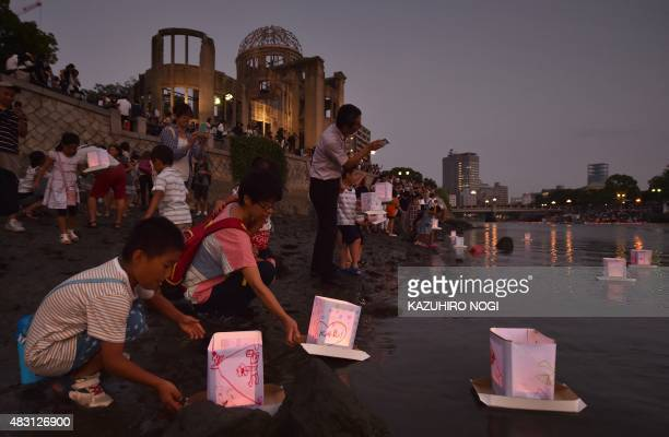 People release paper lanterns into the Motoyasu River in front of the Atomic Bomb Dome in Hiroshima on August 6 2015 Tens of thousands gathered for...